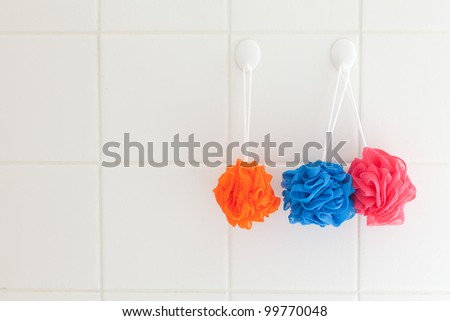 Three soft nylon body scrubbers hanging on the white tiles of a shower wall. - stock photo