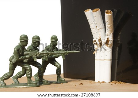 Three soldiers act as a firing squad.  They are shooting three cigarettes.  It's a metaphor for quitting smoking.  It could always be used for a no smoking sign. - stock photo
