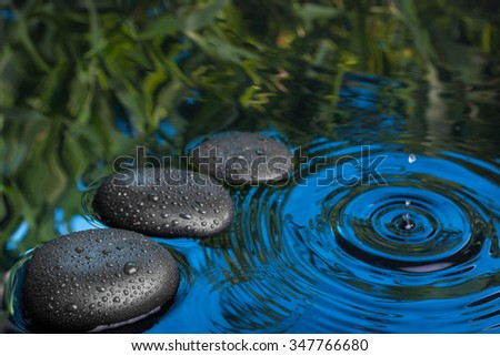 Three spa stone drops lie in the blue water, can be used as background - stock photo