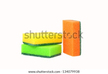 three sponges for washing dishes, standing upright. Two lie horizontally, one vertically standing.