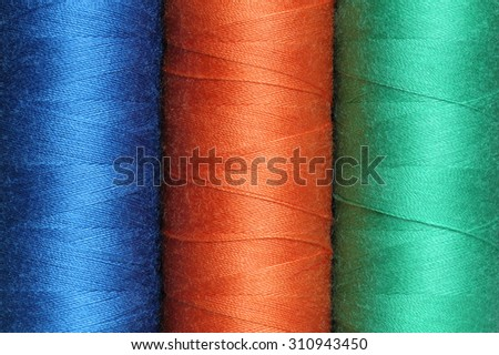 Three spools of color polyester threads - stock photo