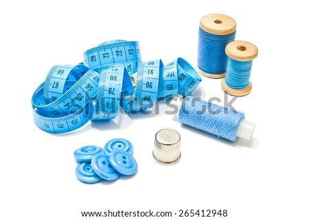 three spools of thread, buttons and meter on white closeup - stock photo
