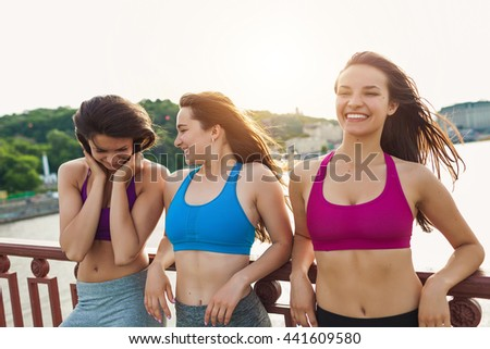 Three sportive pretty women having rest after successful jogging workout outdoors. Cute female running partners resting after hard physical activity Sporty friends portrait - stock photo