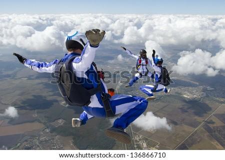 Three sports parachutist build a figure in free fall. - stock photo