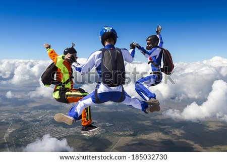 Three sports parachutist build a figure in free fall. - stock photo