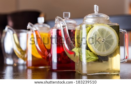three square teapots with different colors fruit tastes of tea - stock photo