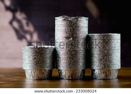 Three stack of aluminium foil pastry molds on wooden table  - stock photo