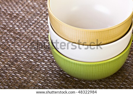 Three Stacked Colorful Bowls On Placemat