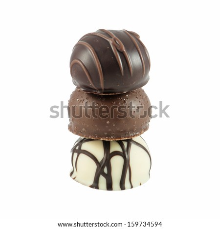 Three stacked gourmet chocolate bonbons isolated on white background. - stock photo