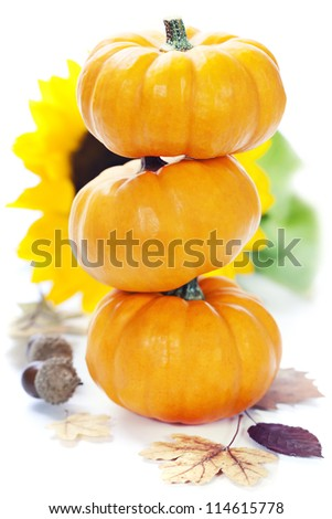 Three stacked mini pumpkins with fall leaves over white - stock photo