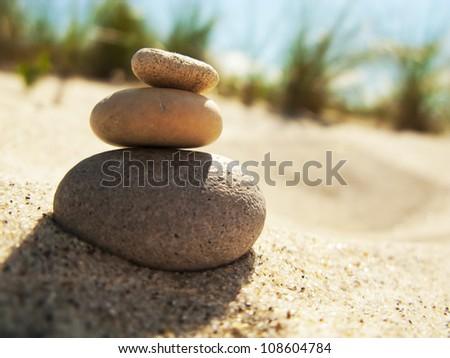 Three stacked stones on the beach - stock photo