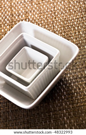 Three Stacked White Bowls On Placemat - stock photo