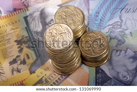 Three stacks of Australian one dollar coins on a background of bank notes. Shallow depth of field focus on tallest stack.