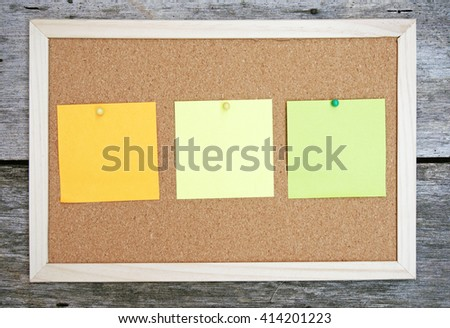 three stick notes on a brown board. shot on a wooden table. orange, yellow, and green notes.