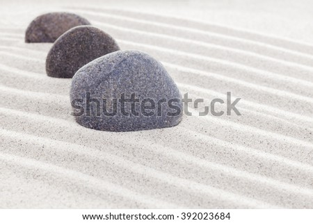 Three stones in sand, spa or zen concept.