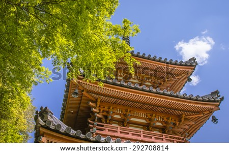 Three storey Japanese style temple pagoda with green maple tree and blue sky at summer. - stock photo