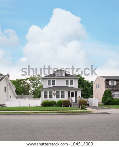 Three Story Suburban Home front yard walkway American Flag Curb Residential Neighborhood Street - stock photo