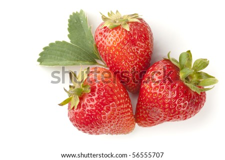 Three strawberries isolated on white background with strawberry plant leaf and soft shadow.