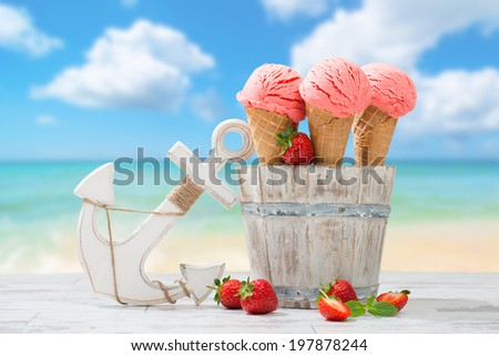 Three strawberry ice creams with fruit at the beach - stock photo