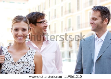 Three strong business people standing together next to a classic office building in the city on a sunny day, smiling. - stock photo