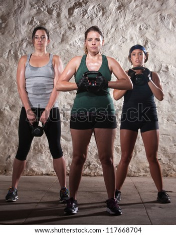 Three strong women lifting kettlebell weights during boot camp workout - stock photo