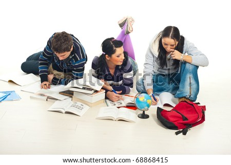 Three student lying down on wooden floor and make their homework