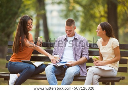 Three students are sitting on bench in park and learning.