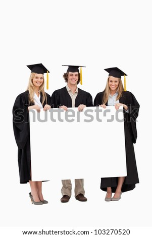 Three students in graduate robe holding a blank sign against white background - stock photo