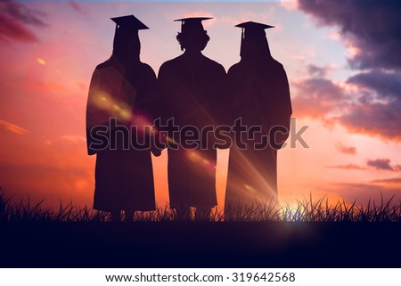 Three students in graduate robe holding a diploma against orange and blue sky with clouds - stock photo