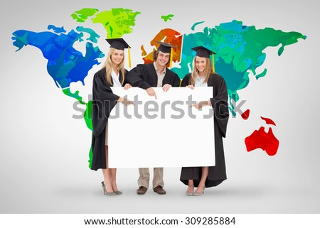 Three students in graduate robe holding and pointing a blank sign against grey vignette - stock photo