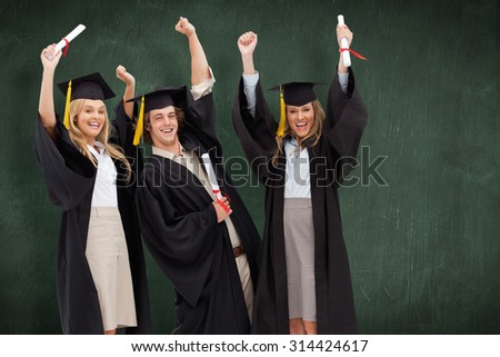 Three students in graduate robe raising their arms against green chalkboard