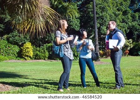 Three students in the park, on their way to college, making fun on a bright, sunny day