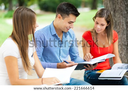 Three students sitting on a bench outdoor - stock photo