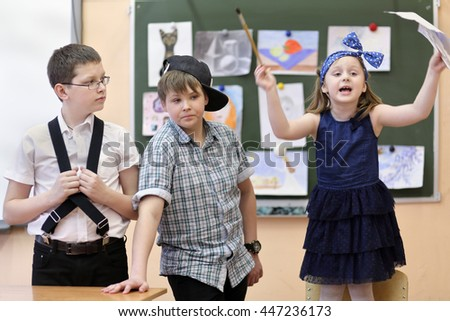three students: two boys and one girl act out scene in class performance at drawing lesson