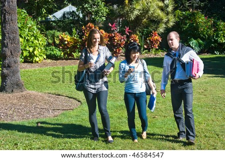 Three students walking through the botanical gardens, on their way to class