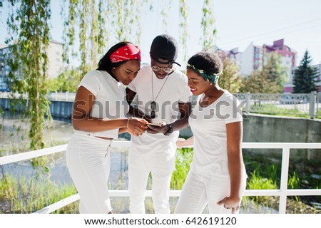 Three stylish and trendy african american friends, wear on white clothes. Street fashion of young black people. Black man with two african girls looking on phone.
