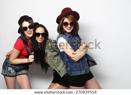 Three stylish sexy hipster girls best friends.Standing together and having fun. Looking at camera. Over gray background. - stock photo