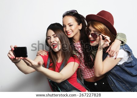 Three stylish sexy hipster girls best friends taking selfie with mobile phone - stock photo