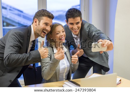 Three successful business people taking a happy Selfie in the office. The Thumbs up - stock photo