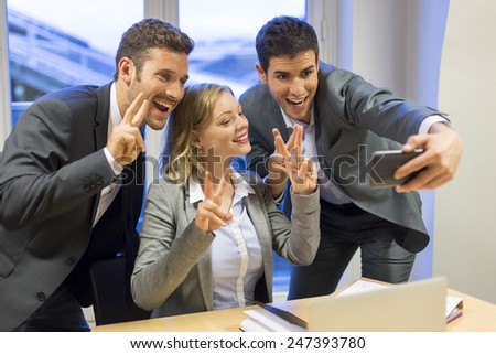 Three successful business people taking a happy Selfie in the office. V victory - stock photo