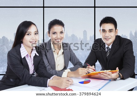 Three successful entrepreneurs sitting in the office and smiling at the camera while discussing financial graph - stock photo
