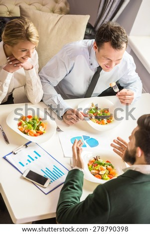 Three successful people sitting at the table and talking about business strategy during business lunch.