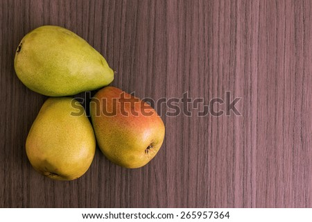Three succulent ripe pears over wood background - stock photo