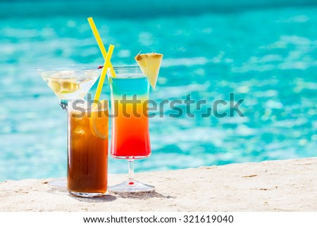 Three summer cocktail by pool. Delicious beverages. Horizontal. Cocktails on the left side - stock photo