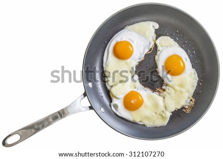 Three Sunny Side Up Fried Eggs, With Edam Cheese Slices, in Teflon Frying Pan, Isolated on White Background. - stock photo