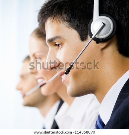 Three support phone operators at workplace - stock photo