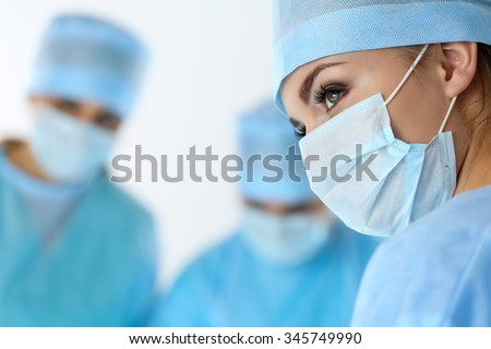 Three surgeons at work operating in surgical theatre saving patient and looking at life monitor. Resuscitation medicine team wearing protective masks saving patient. Surgery and emergency concept - stock photo