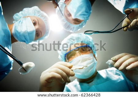 Three surgeons bending over a patient