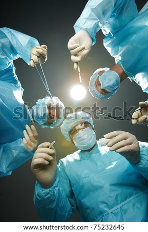 Three surgeons bending over a patient with forceps - stock photo