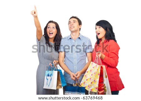 Three surprised friends holding shopping bags ,pointing and looking up isolated on white background - stock photo